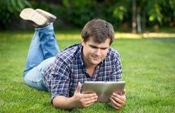 Studente sorridente che per mezzo della compressa digitale su erba al parco Fotografie Stock Libere da Diritti