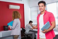 Studente sorridente che per mezzo dello smartphone vicino ai compagni di classe Immagine Stock Libera da Diritti