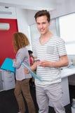 Studente sorridente che per mezzo dello smartphone vicino ai compagni di classe Fotografia Stock