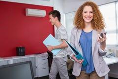 Studente sorridente che per mezzo dello smartphone vicino ai compagni di classe Fotografia Stock Libera da Diritti