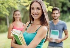 Studente sorridente che posa con i taccuini Fotografie Stock
