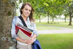 Studente sorridente che si appoggia albero che tiene i suoi libri Fotografie Stock