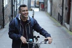 Studente sorridente che si dirige alla città universitaria in bicicletta Fotografie Stock