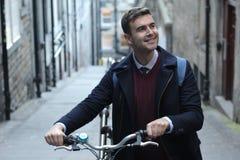 Studente sorridente che si dirige alla città universitaria in bicicletta Fotografia Stock Libera da Diritti