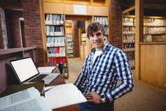 Studente sorridente che si siede nella biblioteca Fotografia Stock