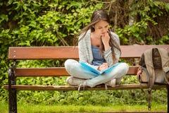 Studente sorridente che si siede sul libro di lettura del banco Fotografie Stock