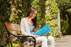 Studente sorridente che si siede sul libro di lettura e del banco Immagini Stock