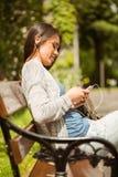 Studente sorridente che si siede sul messaggio di testo del banco sul suo telefono cellulare Fotografia Stock