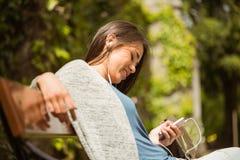 Studente sorridente che si siede sul messaggio di testo del banco sul suo telefono cellulare Immagini Stock