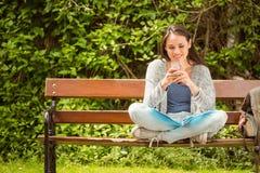 Studente sorridente che si siede sul messaggio di testo del banco sul suo telefono cellulare Immagine Stock Libera da Diritti