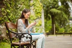 Studente sorridente che si siede sul messaggio di testo del banco sul suo telefono cellulare Fotografia Stock Libera da Diritti