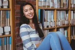Studente sorridente che si siede sul pavimento contro la parete in biblioteca Fotografie Stock