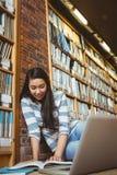 Studente sorridente che si siede sul pavimento contro la parete in biblioteca che studia con il computer portatile ed i libri Immagini Stock