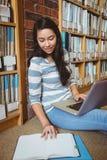 Studente sorridente che si siede sul pavimento contro la parete in biblioteca che studia con il computer portatile ed i libri Immagine Stock
