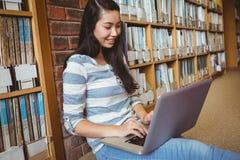 Studente sorridente che si siede sul pavimento contro la parete in biblioteca facendo uso del computer portatile Immagine Stock Libera da Diritti