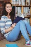 Studente sorridente che si siede sul pavimento contro la parete in libro di lettura delle biblioteche Fotografia Stock Libera da Diritti