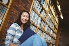 Studente sorridente che si siede sul pavimento contro la parete in libro di lettura delle biblioteche Immagini Stock Libere da Diritti
