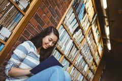 Studente sorridente che si siede sul pavimento contro la parete in libro di lettura delle biblioteche Fotografie Stock