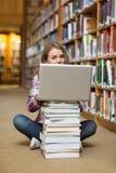 Studente sorridente che si siede sul pavimento delle biblioteche facendo uso del computer portatile sul mucchio dei libri Fotografia Stock Libera da Diritti