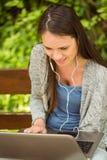 Studente sorridente che si siede sulla musica e sul per mezzo d'ascolto del banco del computer portatile Immagini Stock