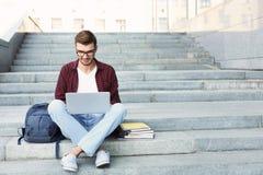 Studente sorridente che si siede sulle scale facendo uso del computer portatile Immagine Stock