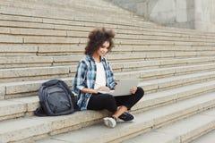 Studente sorridente che si siede sulle scale facendo uso del computer portatile Fotografia Stock