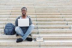Studente sorridente che si siede sulle scale facendo uso del computer portatile Immagini Stock