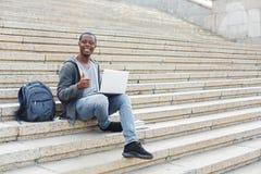 Studente sorridente che si siede sulle scale facendo uso del computer portatile Fotografie Stock Libere da Diritti