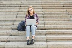 Studente sorridente che si siede sulle scale facendo uso del computer portatile Fotografie Stock
