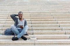 Studente sorridente che si siede sulle scale facendo uso della compressa Immagini Stock