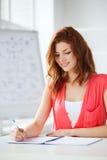 Studente sorridente con i manuali alla scuola Immagini Stock