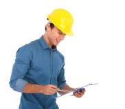 Studente sorridente di ingegneria di costruzione che legge le sue note Immagine Stock Libera da Diritti