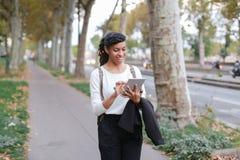 Studente sorridente femminile nero che per mezzo della compressa e camminando sulla via con gli alberi Immagine Stock