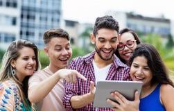 Studente spagnolo dei pantaloni a vita bassa con il computer della compressa e gruppo di incoraggiare gli studenti internazionali fotografie stock