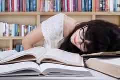 Studente stanco alla biblioteca Immagine Stock