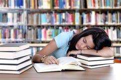 Studente stanco che dorme allo scrittorio in una biblioteca Fotografia Stock Libera da Diritti