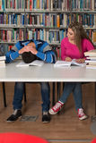 Studente stanco che dorme nella biblioteca Immagine Stock Libera da Diritti