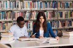 Studente stanco che dorme nella biblioteca Fotografia Stock Libera da Diritti