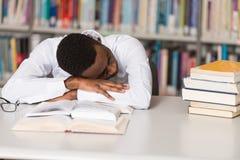Studente stanco che dorme nella biblioteca Fotografia Stock