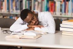 Studente stanco che dorme nella biblioteca Immagini Stock