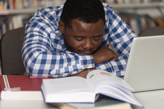 Studente stanco che dorme nella biblioteca Fotografie Stock