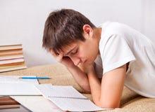 Studente stanco che lavora a casa Immagine Stock