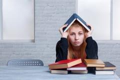 Studente stanco della ragazza, sedentesi ad una tavola accanto ad un mucchio dei libri Apprendimento del concetto Fotografie Stock