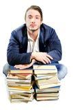 Studente stanco di studio sui mucchi dei libri Immagine Stock
