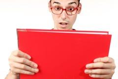 Studente stupito con il taccuino rosso ed i vetri rossi Fotografie Stock Libere da Diritti