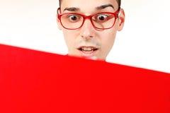 Studente stupito con il taccuino rosso ed i vetri rossi Immagini Stock Libere da Diritti