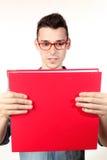 Studente stupito con il taccuino rosso ed i vetri rossi Immagini Stock