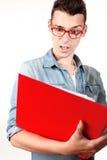 Studente stupito con il taccuino rosso ed i vetri rossi Immagine Stock
