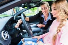 Studente sulla ruota dell'automobile nella lezione di azionamento con il suo insegnante Fotografia Stock Libera da Diritti