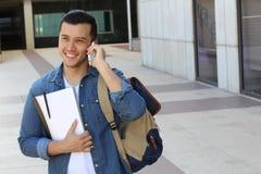 Studente sveglio che chiama dal telefono sulla città universitaria con lo spazio della copia Immagine Stock